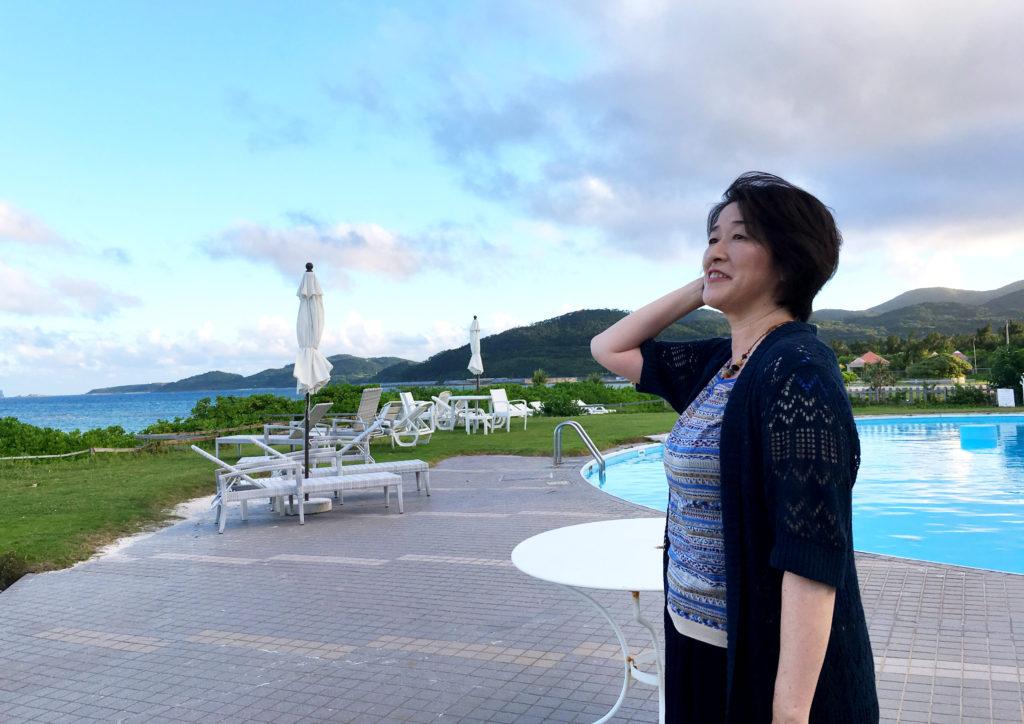 久米島の美しい海を眺める理絵さん