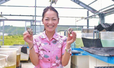 久米島で牡蠣の陸上養殖に取り組む株式会社ジーオー・ファーム社長、鷲足恭子さん。両手に抱えるのはまさに養殖中の牡蠣!